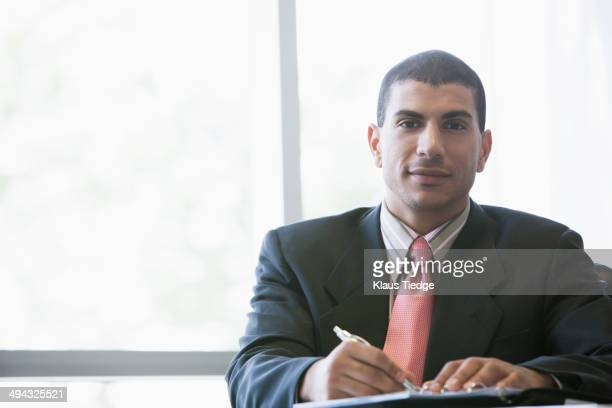 Hispanic businessman making notes in office