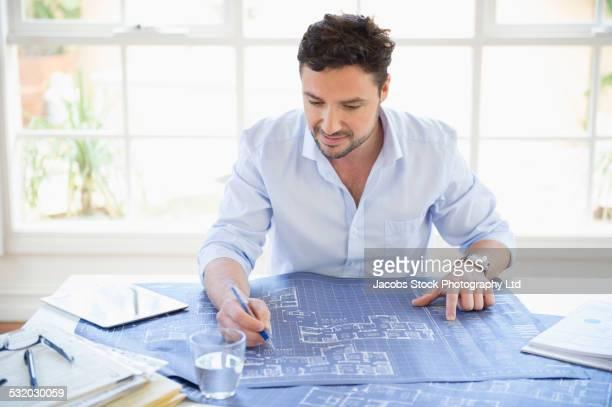Hispanic businessman marking blueprints at desk in office