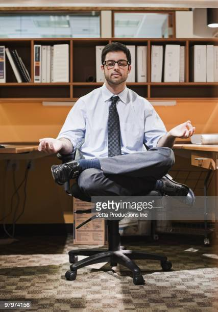 Hispanic businessman meditating at desk