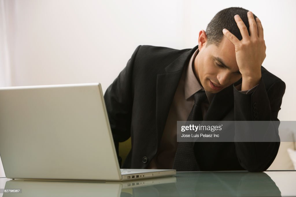 Hispanic businessman on laptop with head in hands : Stock Photo
