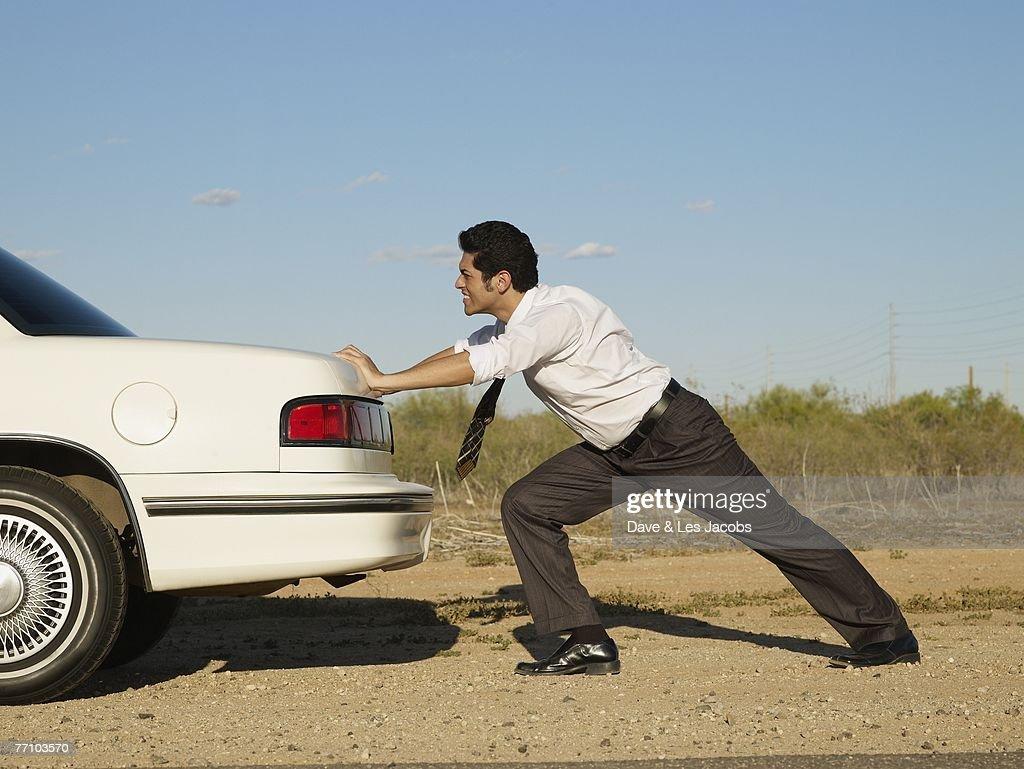 Hispanic businessman pushing back of car