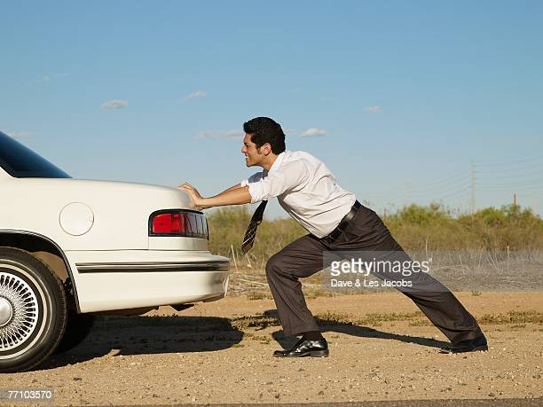 Hispanic businessman pushing back of car