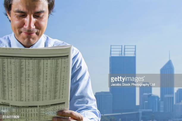 Hispanic businessman reading newspaper in front of Perth city skyline, Perth, Western Australia, Australia
