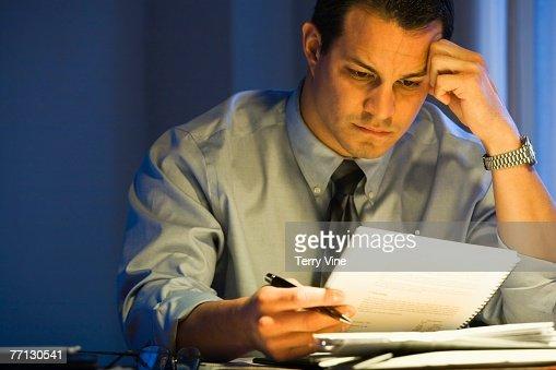 Hispanic businessman reading paperwork : Stock Photo