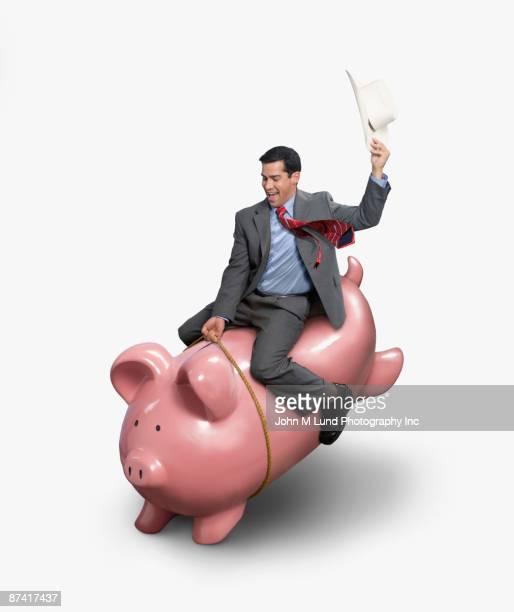 Hispanic businessman riding piggybank