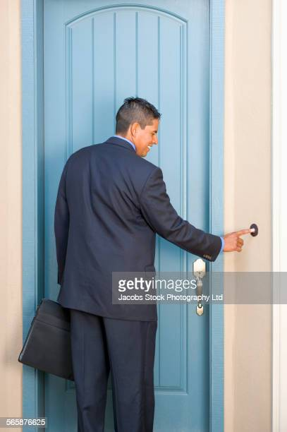 Hispanic businessman ringing doorbell
