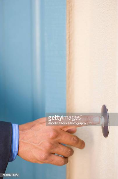 Hispanic businessman ringing doorbell
