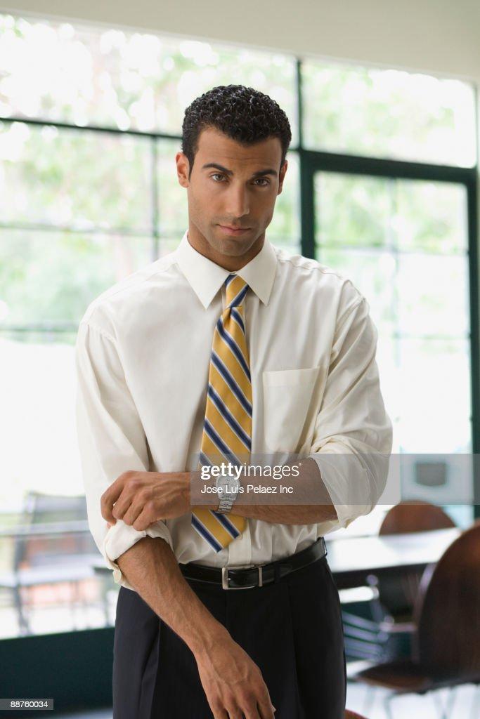 Hispanic businessman rolling up sleeves