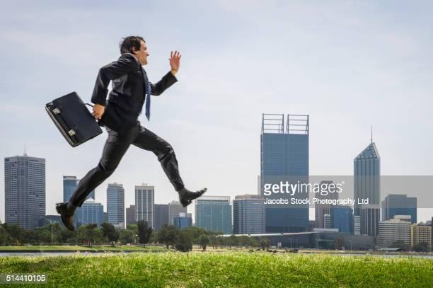 Hispanic businessman running in park, Perth, Western Australia, Australia