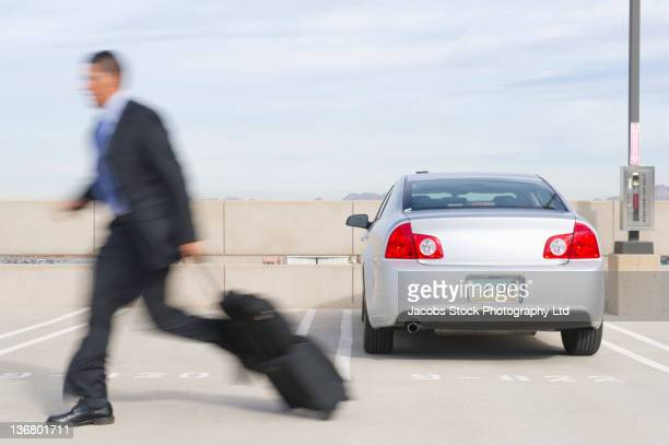 Hispanic businessman running in parking lot with luggage