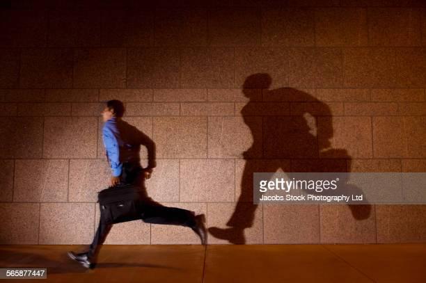 Hispanic businessman running in spotlight on city sidewalk at night