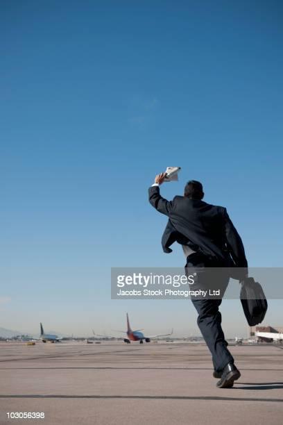 Hispanic businessman running on airport tarmac