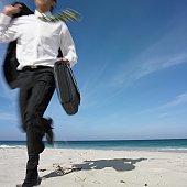 Hispanic businessman running on beach