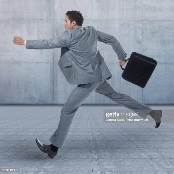 Hispanic businessman running on concrete