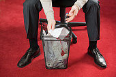Hispanic businessman searching in a wastepaper basket