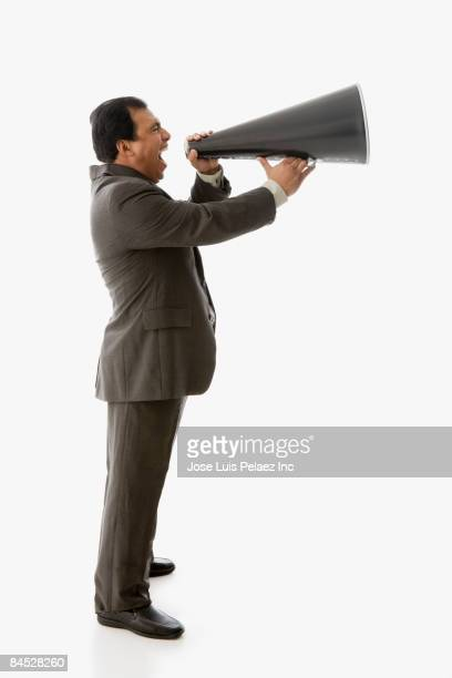 Hispanic businessman shouting into bull horn