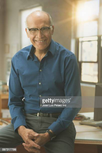 Hispanic businessman smiling in office