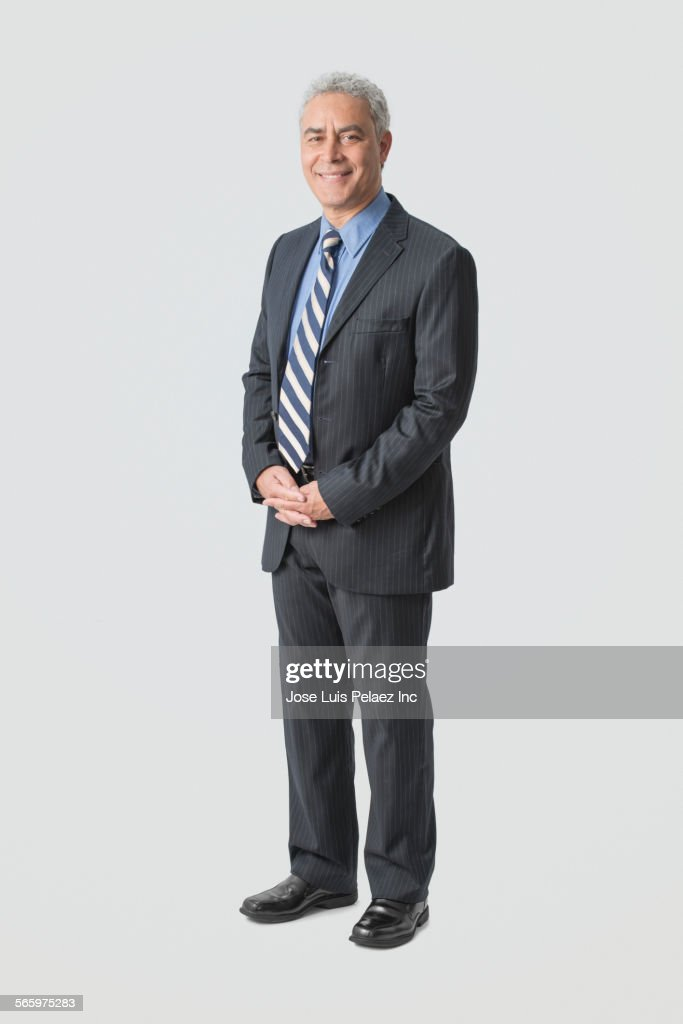 Hispanic businessman smiling with hands clasped : Stock-Foto