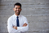Hispanic Businessman Standing Against Wall In Modern Office