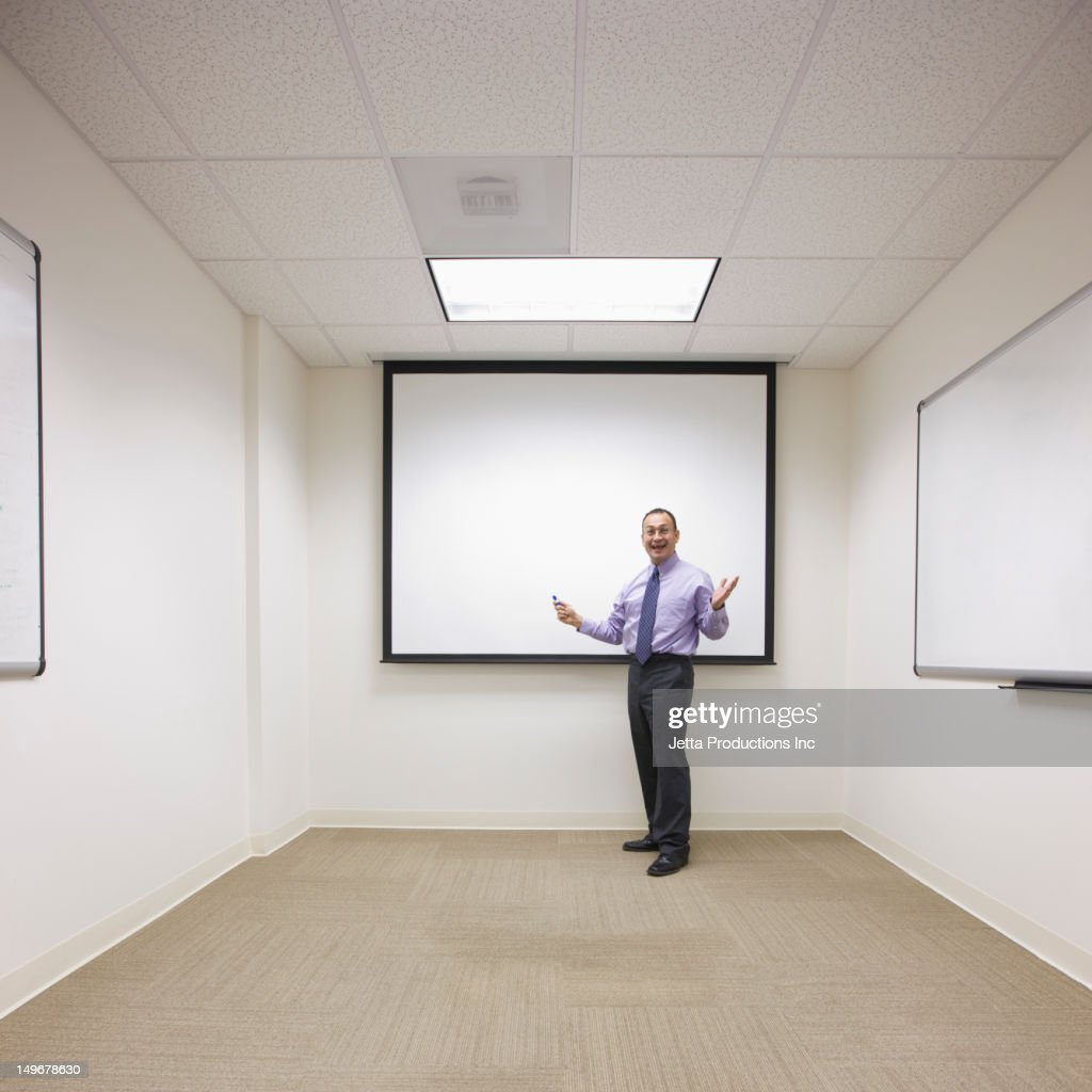 Hispanic businessman standing by screen in office conference room
