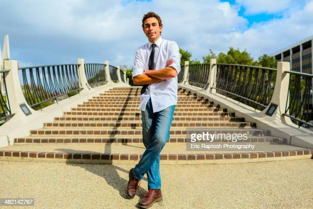Hispanic businessman standing by urban steps