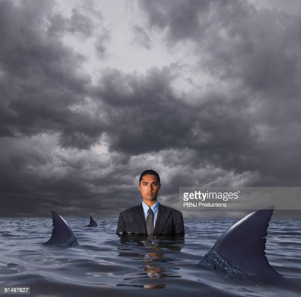 Hispanic businessman standing in water with sharks
