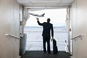 Hispanic businessman standing on jetway waving