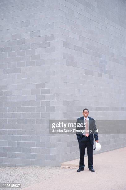 Hispanic businessman standing on sidewalk with hard-hat