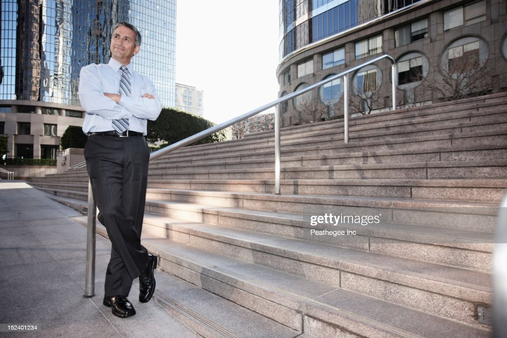 Hispanic businessman standing outdoors with arms crossed : Stock Photo