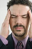 Hispanic businessman suffering from a headache