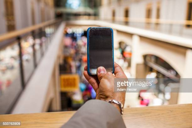 Hispanic businessman taking cell phone photograph from upper level