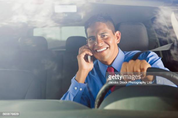 Hispanic businessman talking on cell phone and driving car