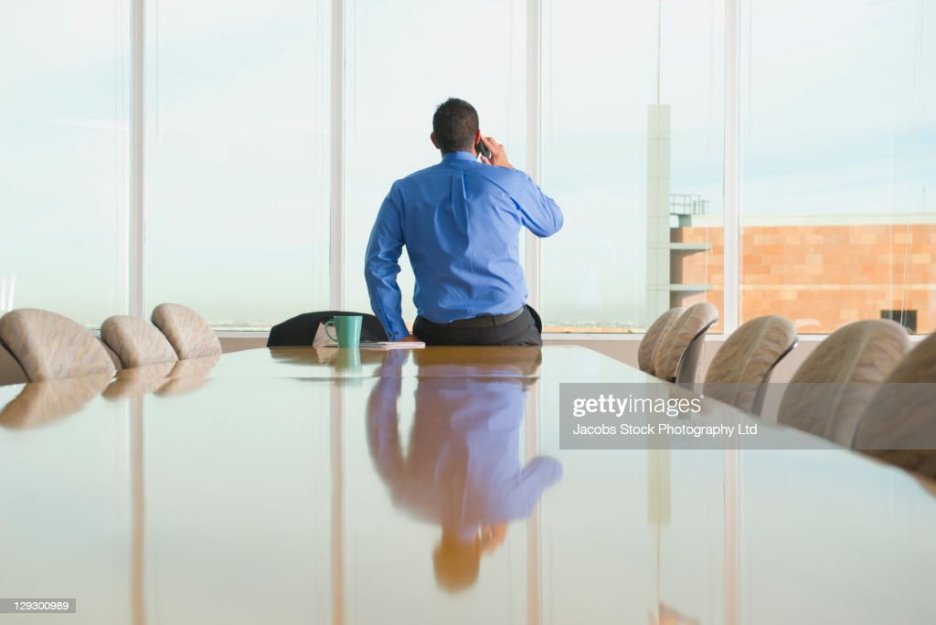Hispanic businessman talking on cell phone in conference room : Stock Photo