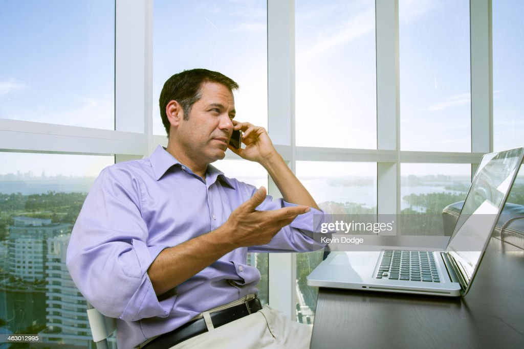 Hispanic businessman talking on cell phone : Stock Photo