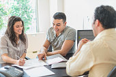 Hispanic businessman talking to clients in office
