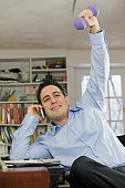 Hispanic businessman using a mobile phone and exercising with weight
