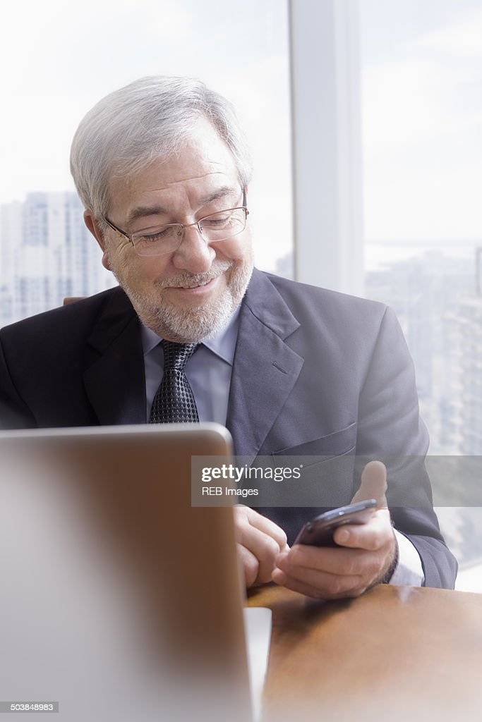 Hispanic businessman using cell phone at desk