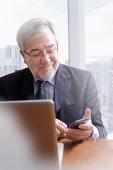 Hispanic businessman using cell phone at desk