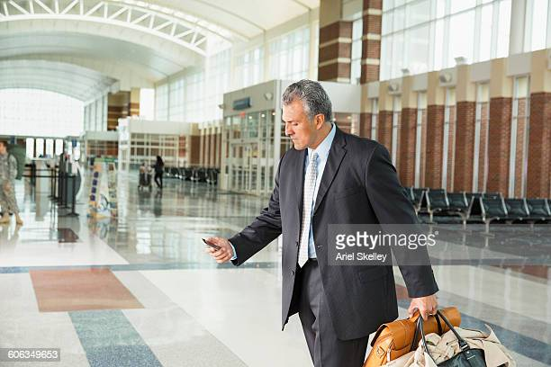 Hispanic businessman using cell phone in airport