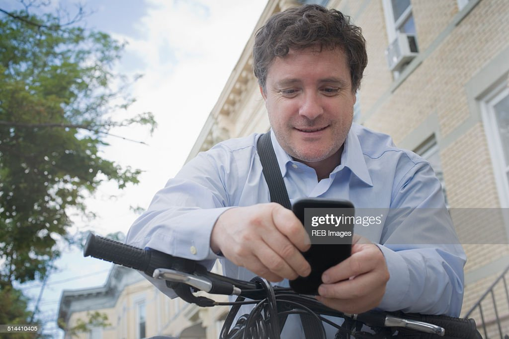 Hispanic businessman using cell phone on bicycle on city street