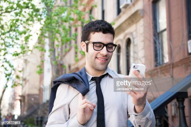 Hispanic businessman using cell phone outside