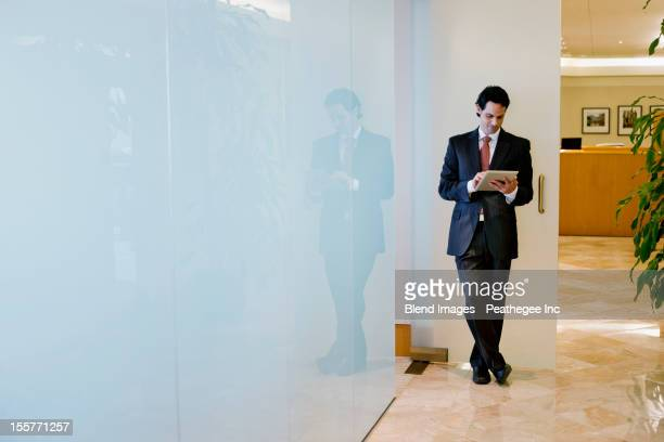 Hispanic businessman using digital tablet in office corridor