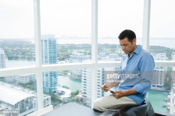 Hispanic businessman using digital tablet in office