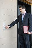 Hispanic businessman using elevator