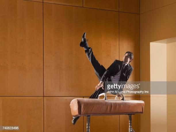 Hispanic businessman using pommel horse
