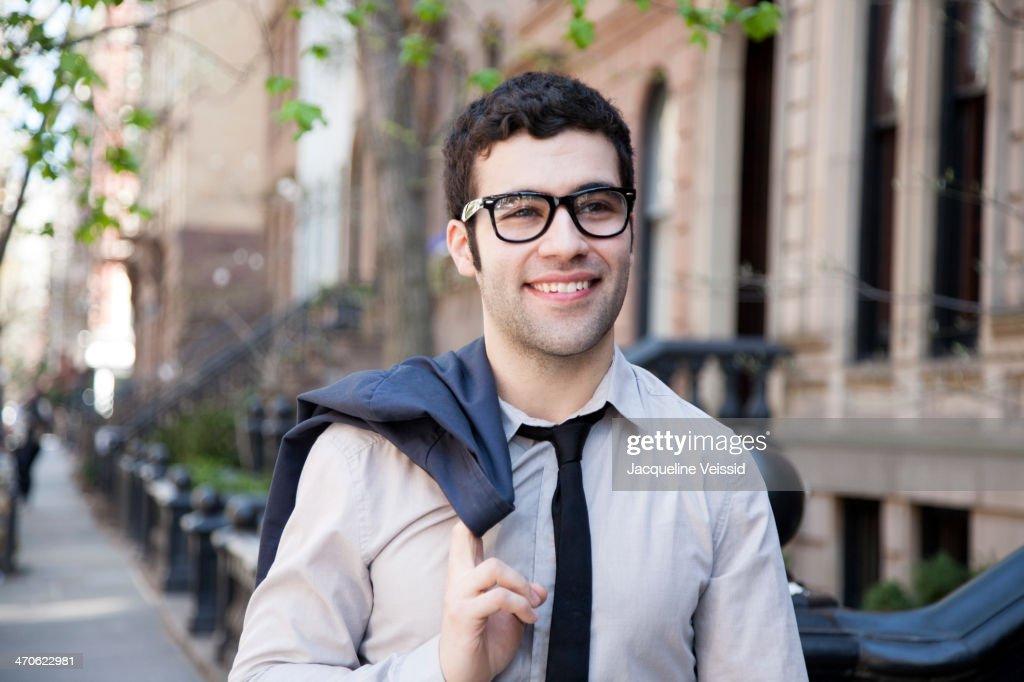 Hispanic businessman walking on city sidewalk : Stock Photo