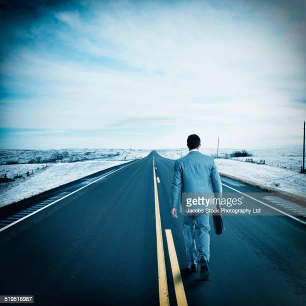 Hispanic businessman walking on remote road