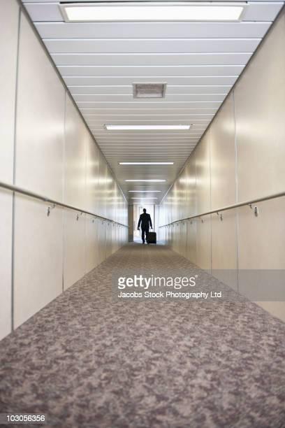 Hispanic businessman walking through jetway
