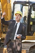 Hispanic businessman wearing a hardhat standing in front of a bulldozer