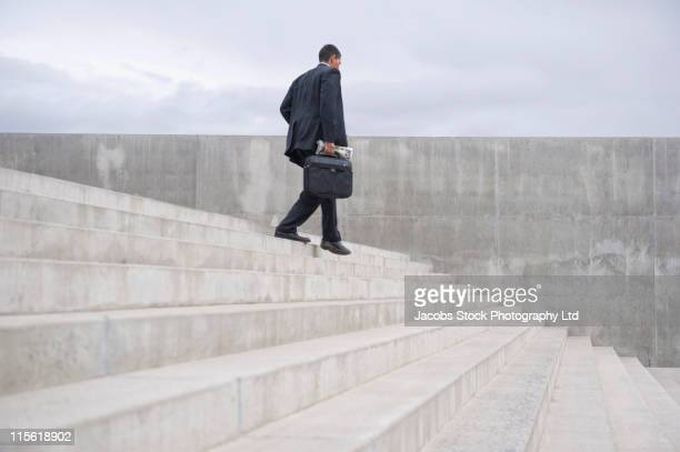 Hispanic businessman with briefcase walking down stairs